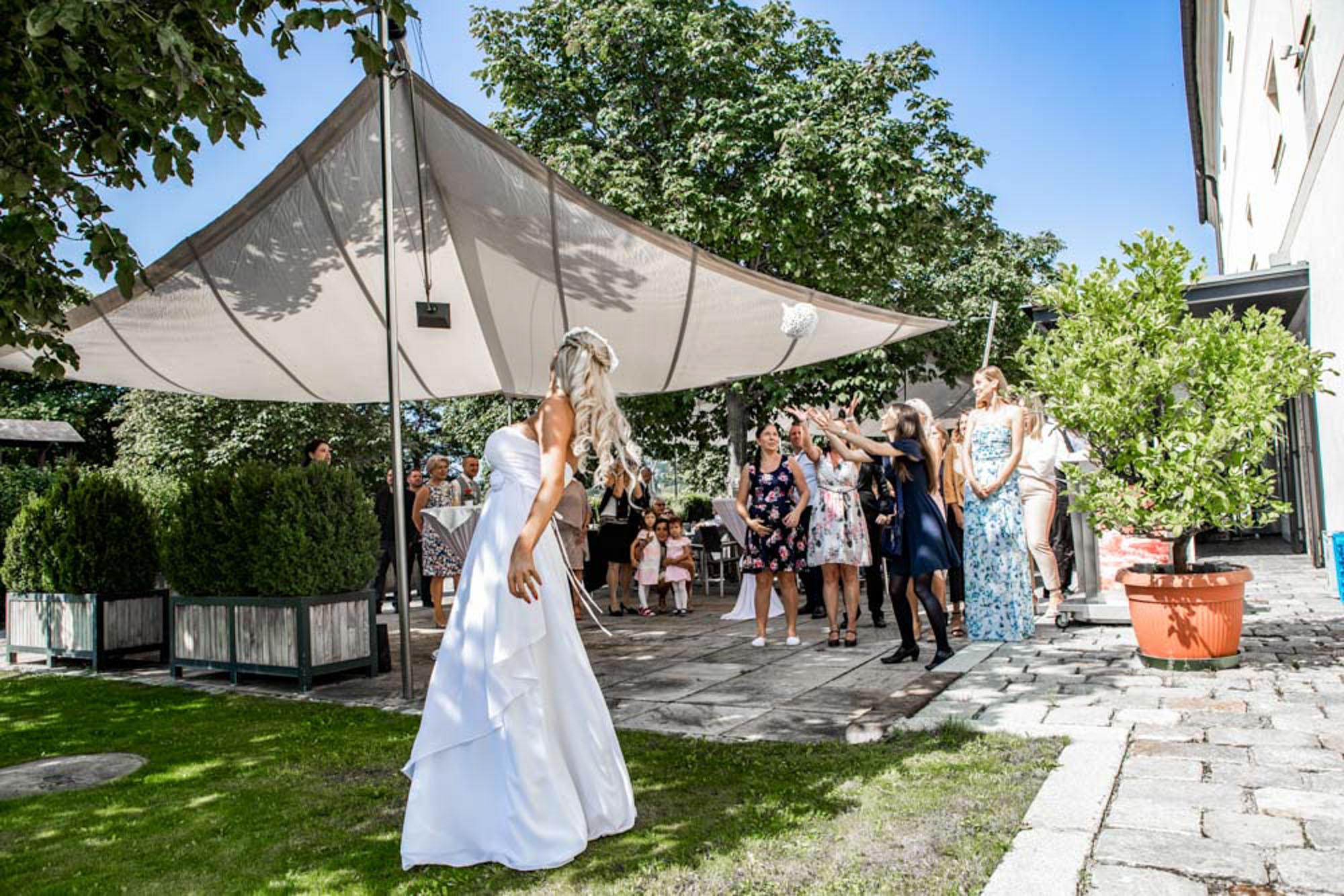 Hochzeitsfotografie Outdoor Braut wirft Strauß